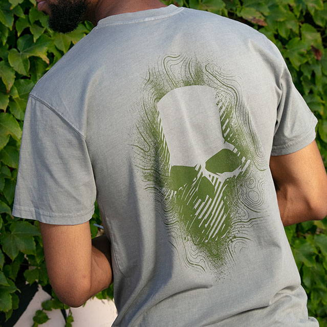 Gray man t-shirt with green skull graphic.