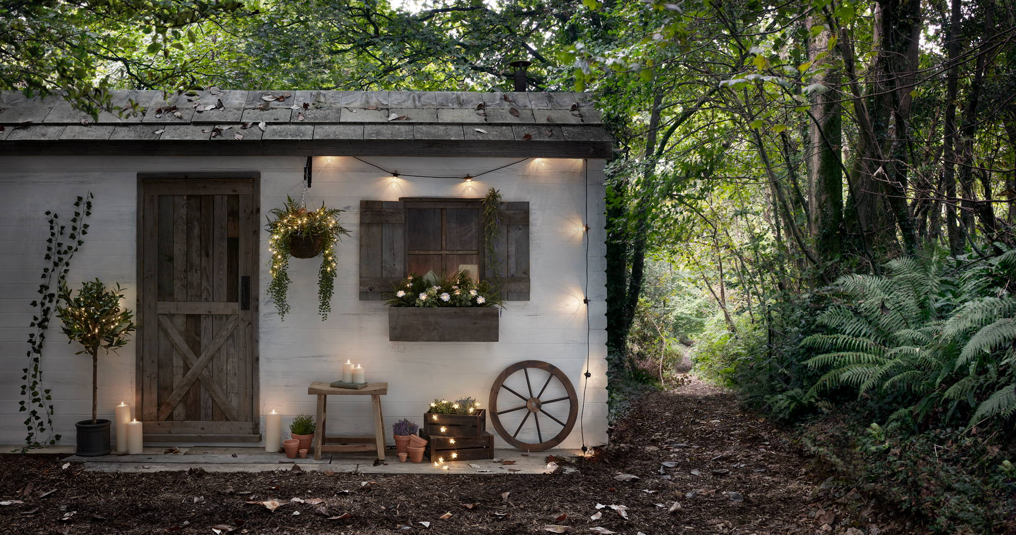 Woodland cabin setting with festoon lights, fairy lights and outdoor candles displayed