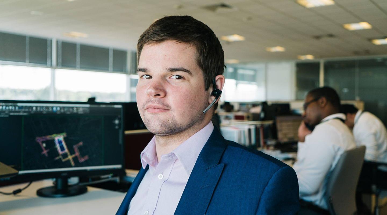 En mann bruker en Tobii Dynavox øyestyringsenhet til å betjene datamaskinen sin på jobb
