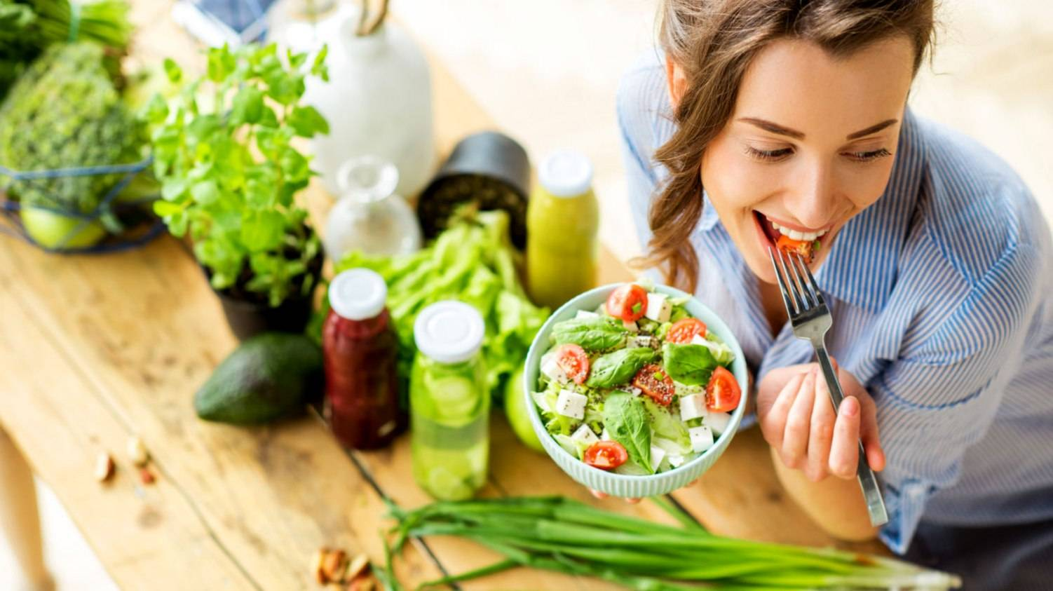 Featured | Young and happy woman eating healthy salad sitting on the table with green fresh ingredients indoors | How To Get Started On Vegan Keto Diet - The Ultimate Guide