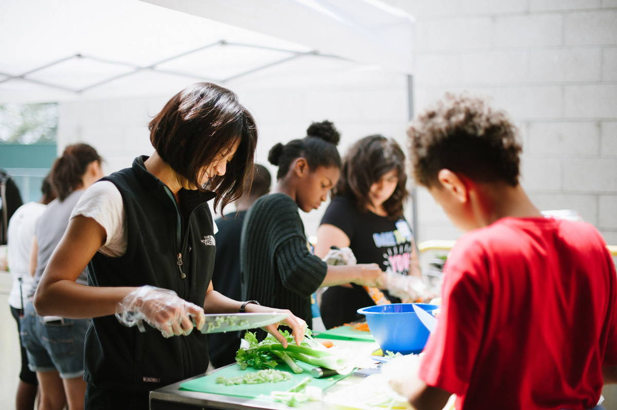Volunteers teaching youth how to cook.