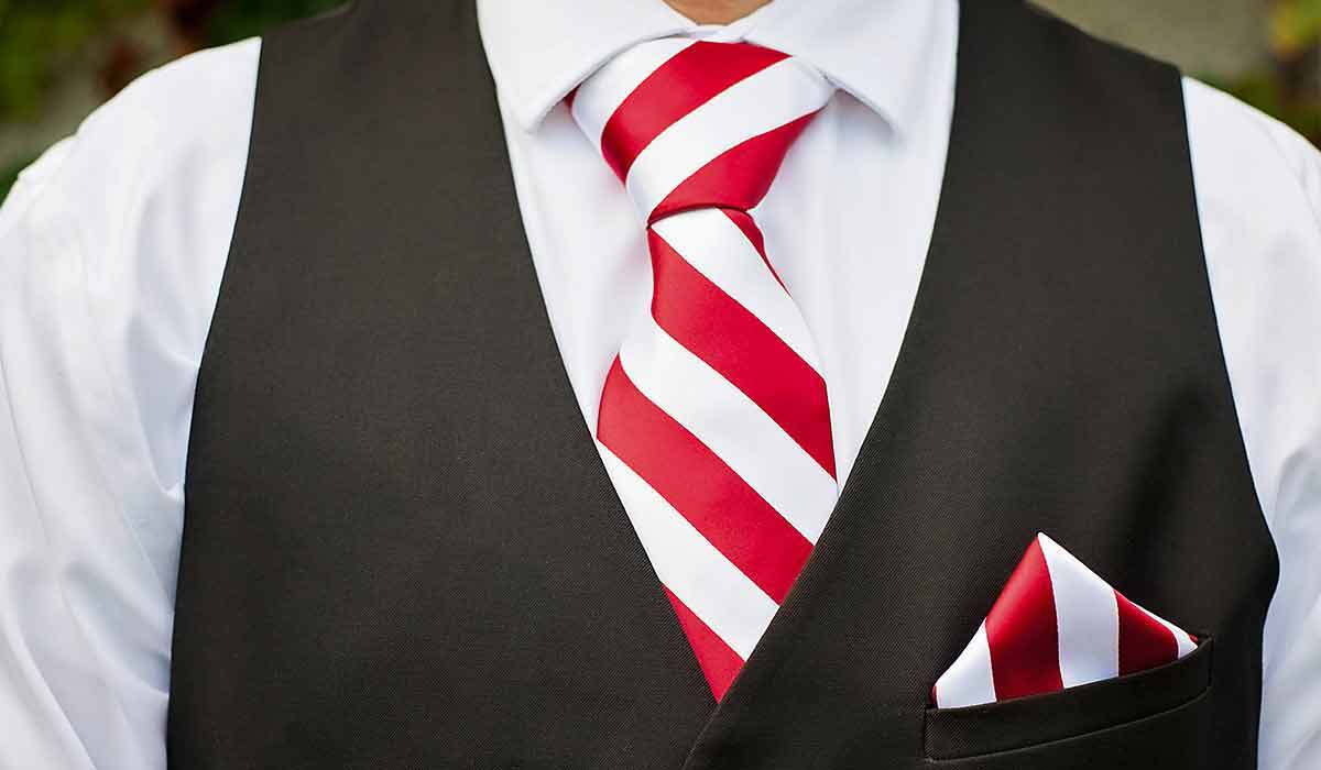 Red and white striped Christmas ties with black vest.
