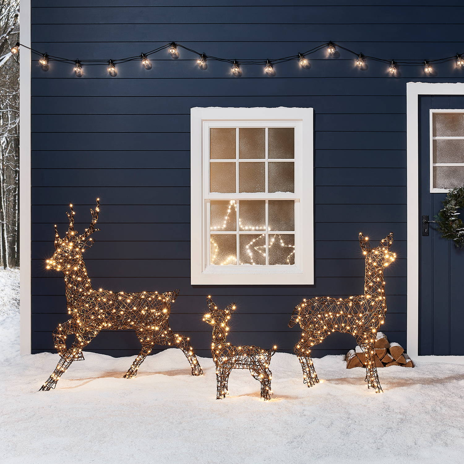 Rattan Light Up Reindeer Family infront of a house decorated for Christmas