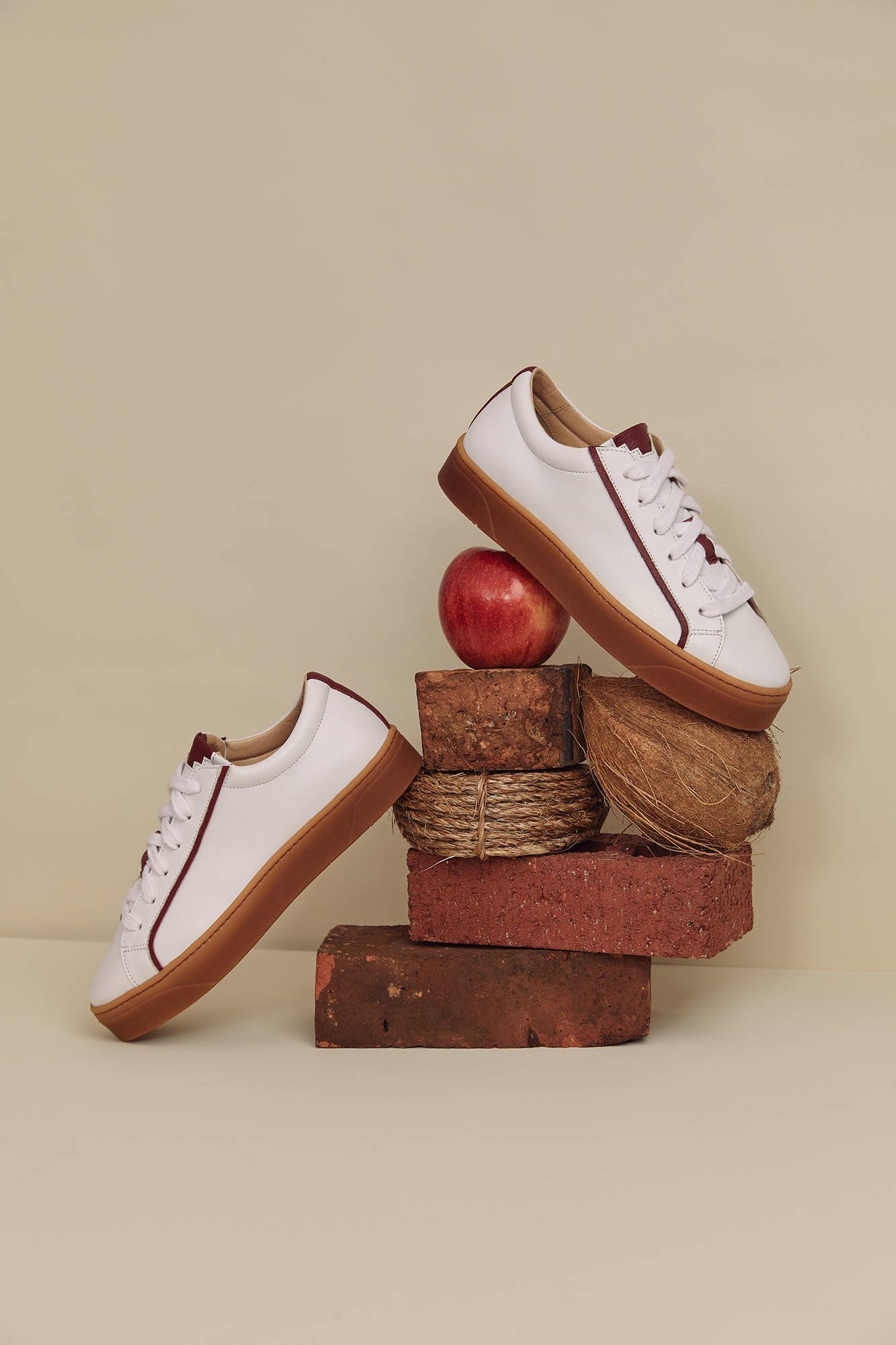 Apple leather and coconut husk plant-based and vegan sustainable sneakers from Sylven New York. The Mel in white vegan apple leather pictured with an apple, bricks,  and rope