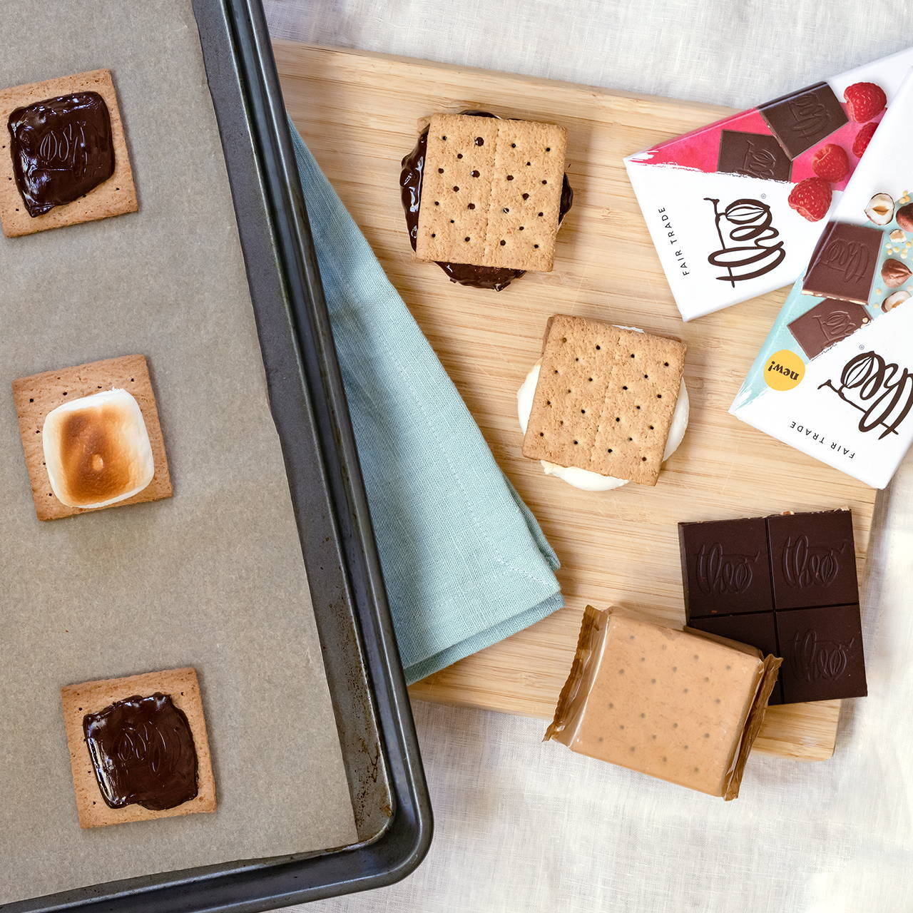 Baking tray fresh from the oven with toasted marshmallows and melted chocolate on graham crackers for oven-baked s'mores next to assembled s'mores on a cutting board.