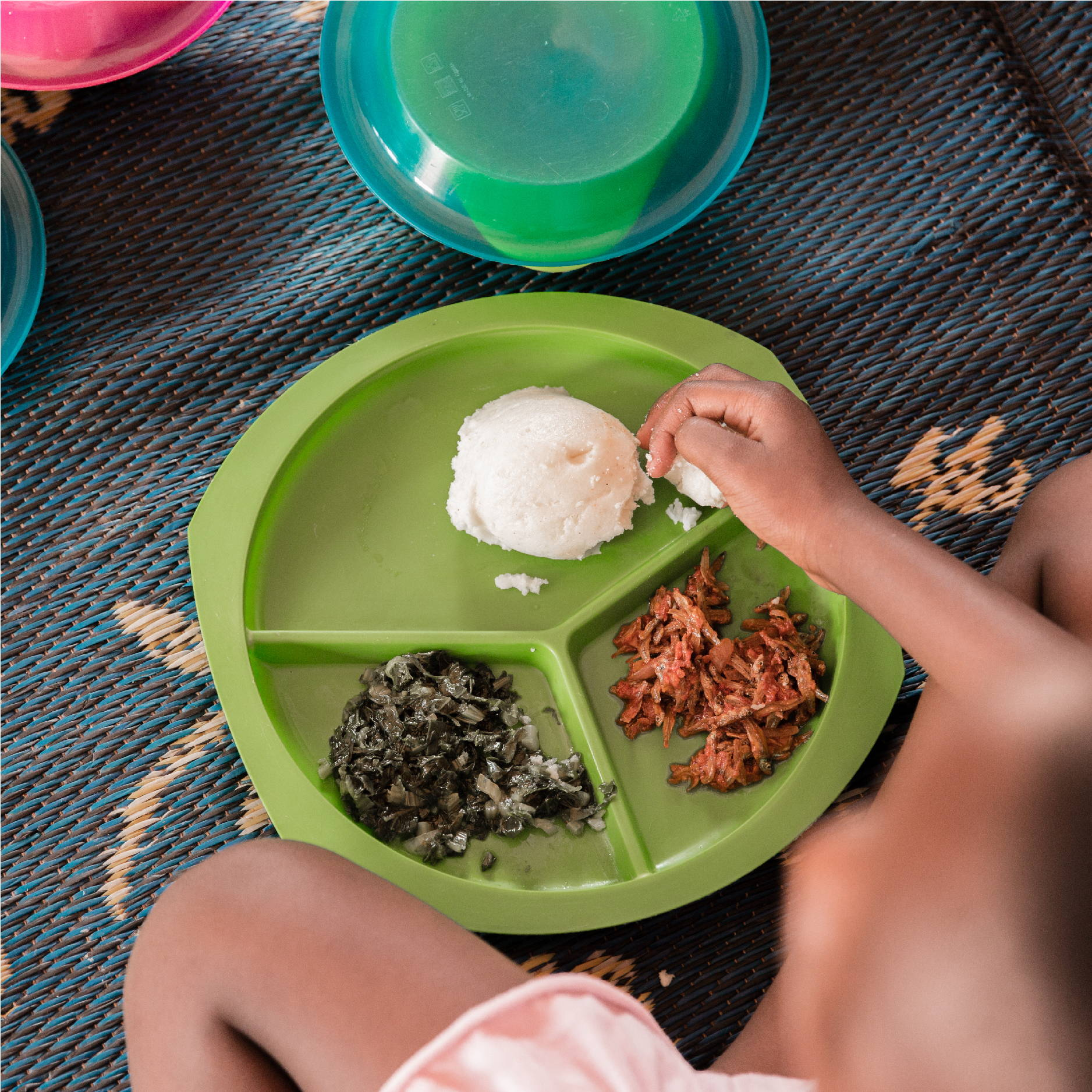A girl is seen eating on a blue straw mat from a green plate. It is a traditional Zambian meal containing nshima