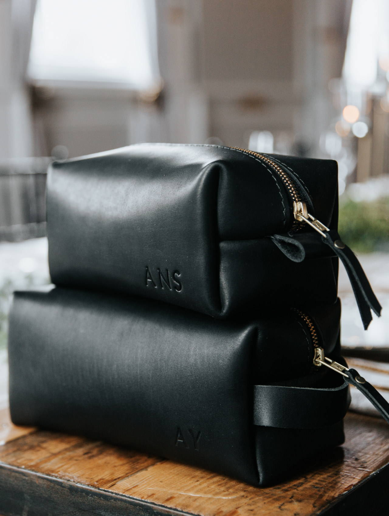 a stack of black handmade leather dopp kit by portland leather goods