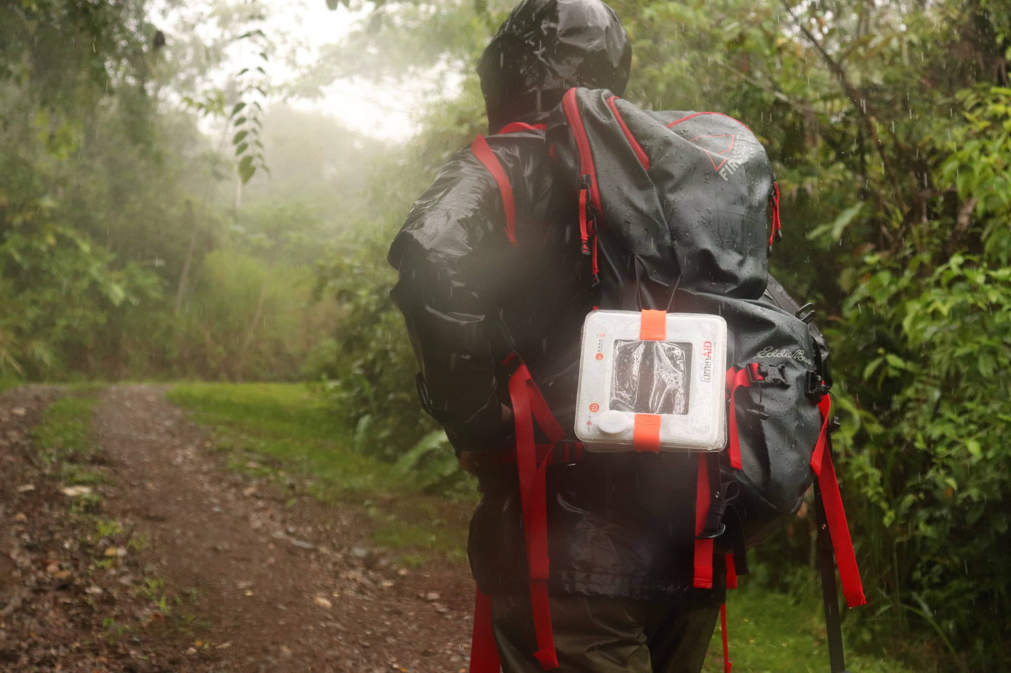 Man backpacking in rain with light on backpack.