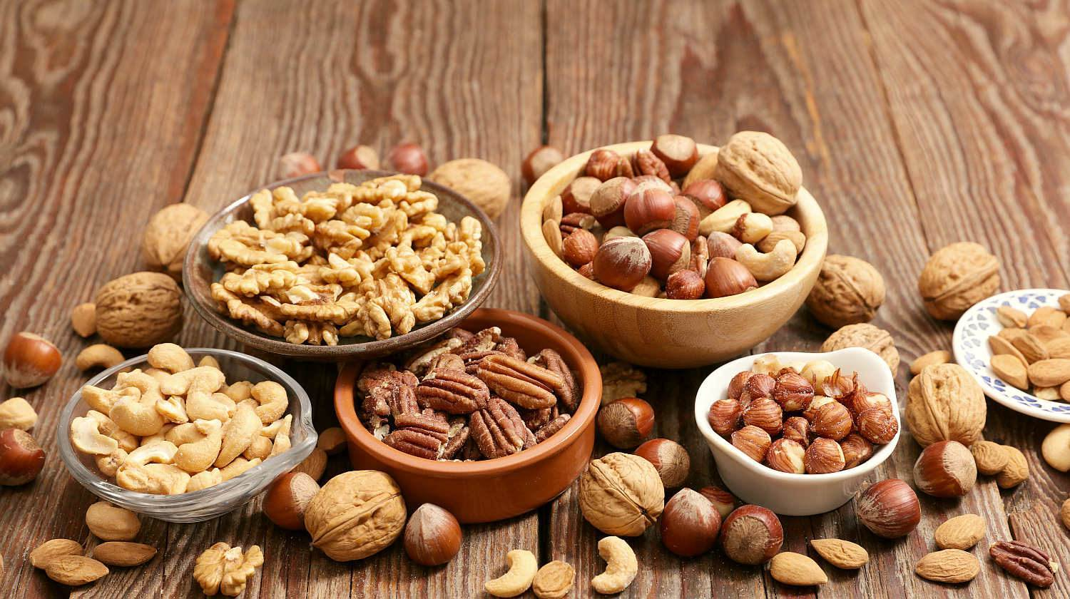 Assorted nut on wooden background | What's The Difference Between Various Nuts and Seeds? | types of nuts | Featured
