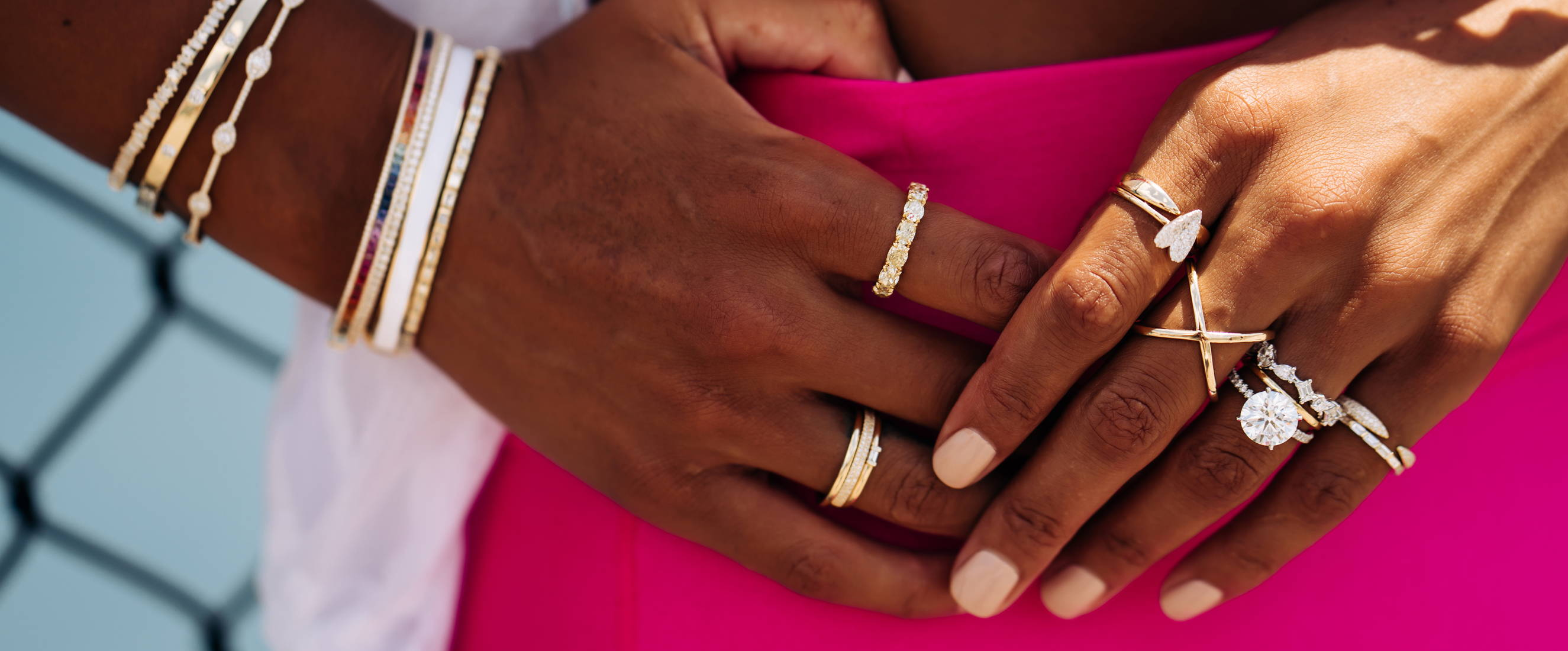 Close up of modeling wearing various Ring Concierge rings and bangles in a neon workout outfit