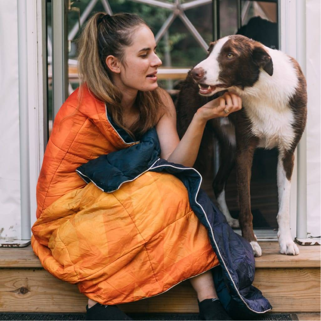 Woman with orange rumpl blanket and her dog