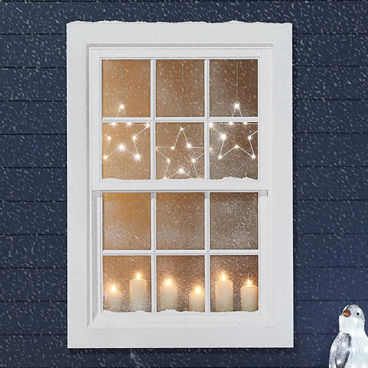 A outdoor view of a blue house at Christmas. In the window there are candles and star lights hanging above.
