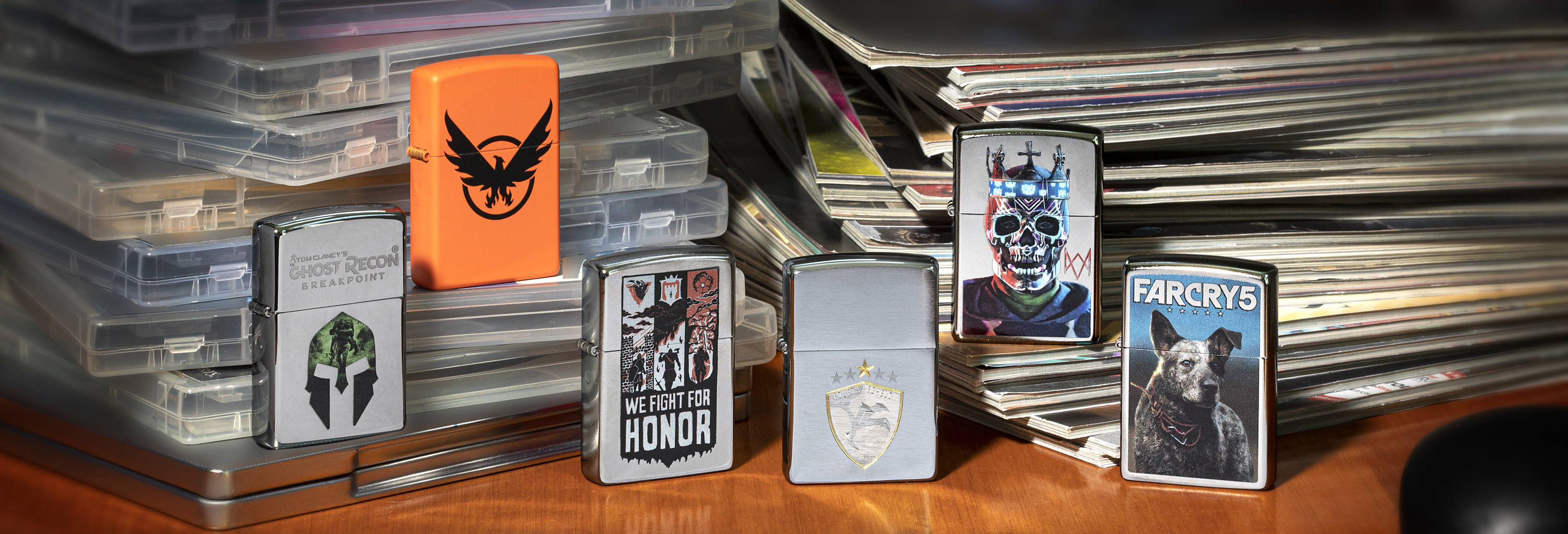 All Ubisoft Web Debut lighters standing staggered on a desk with magazines and game cases