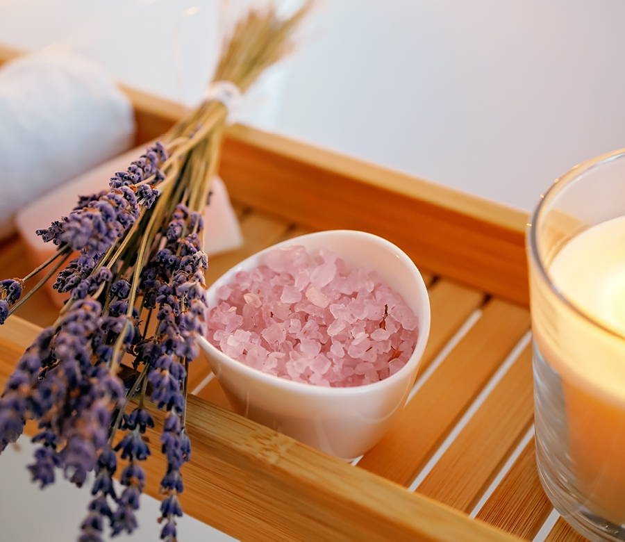 bath caddy with lavender stems, small bowl of pink sea salt, and a candle