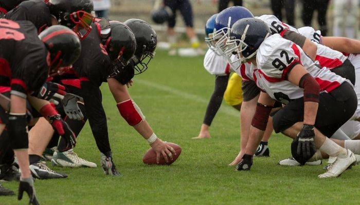 Two football teams playing football on field