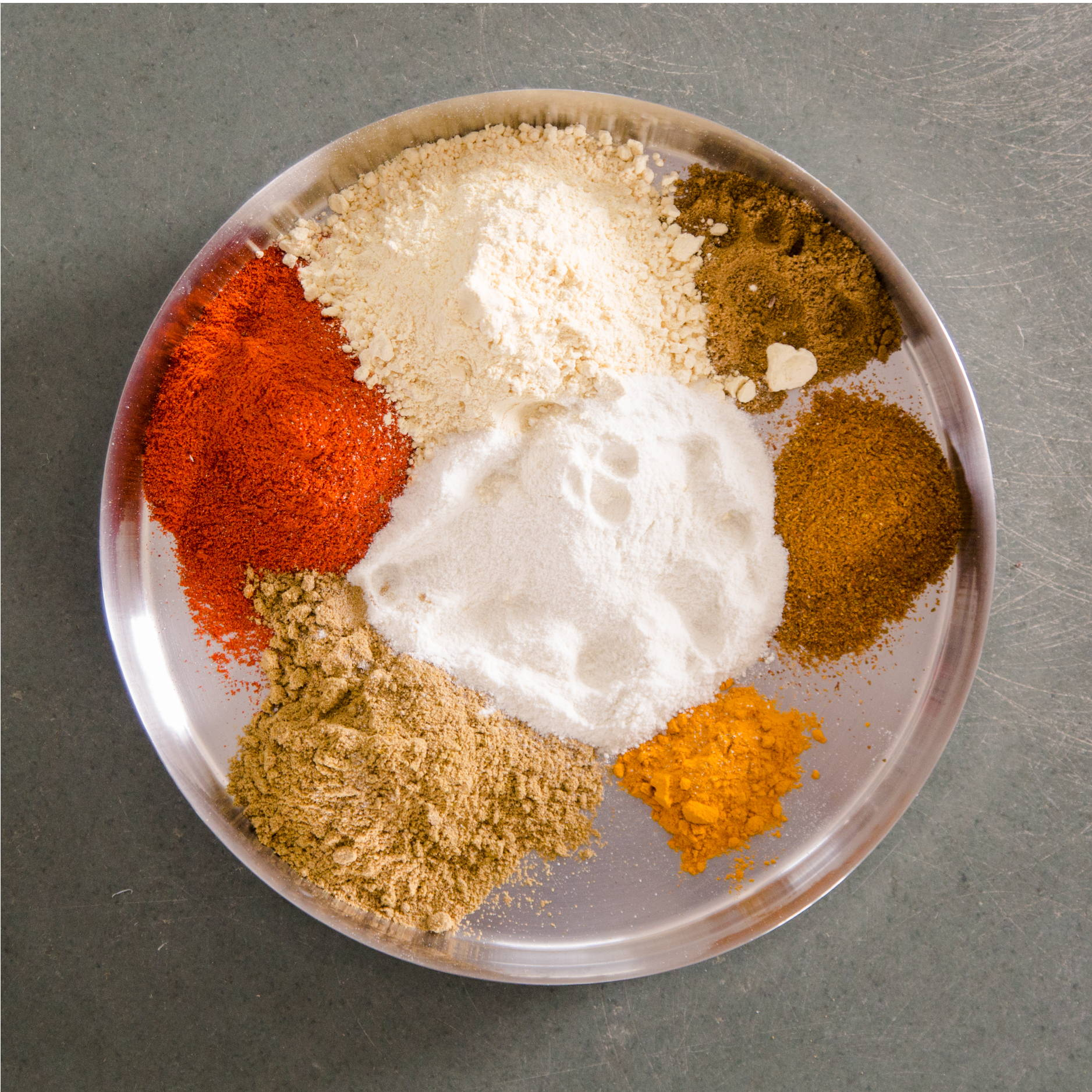A silver plate sits on a concrete floor. It is holding piles of different Indian spices such as curry, turmeric, and cayenne.