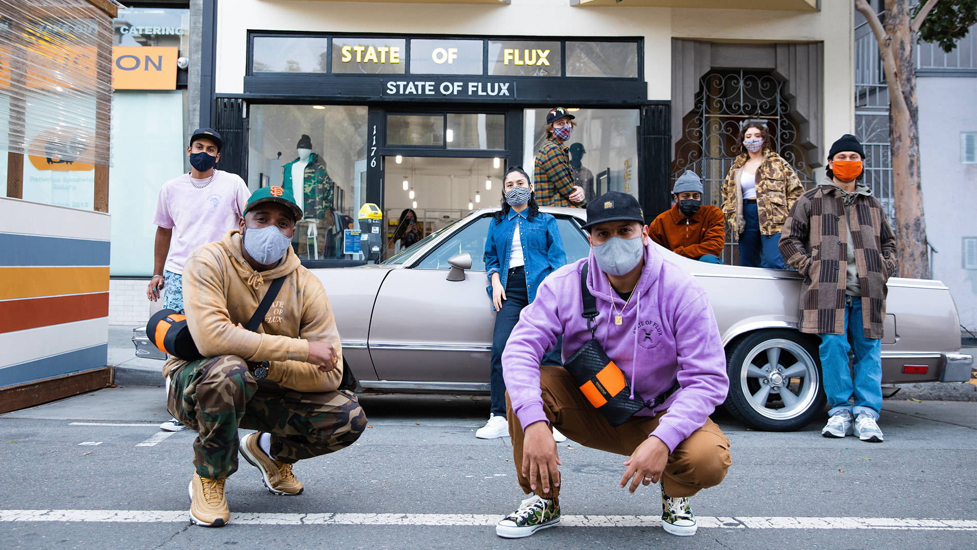Image of multiple Timbuk2 and State Of Flux employees standing in front of the State Of Flux store in the Mission District of San Francisco. Two of them are crouched in front of a truck and are wearing the Mini Hustle Duffel State Of Flux Collab edition.