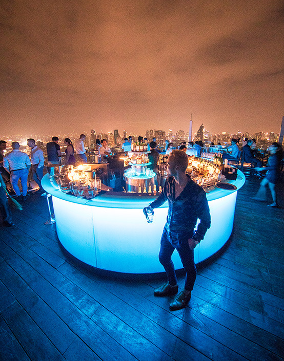 man standing by bar of city rooftop party