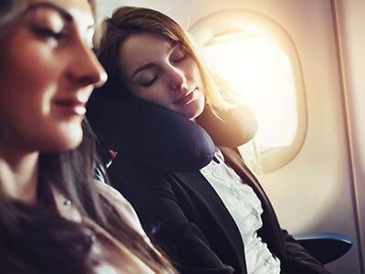 Frau im Flugzeug mit Reisekissen