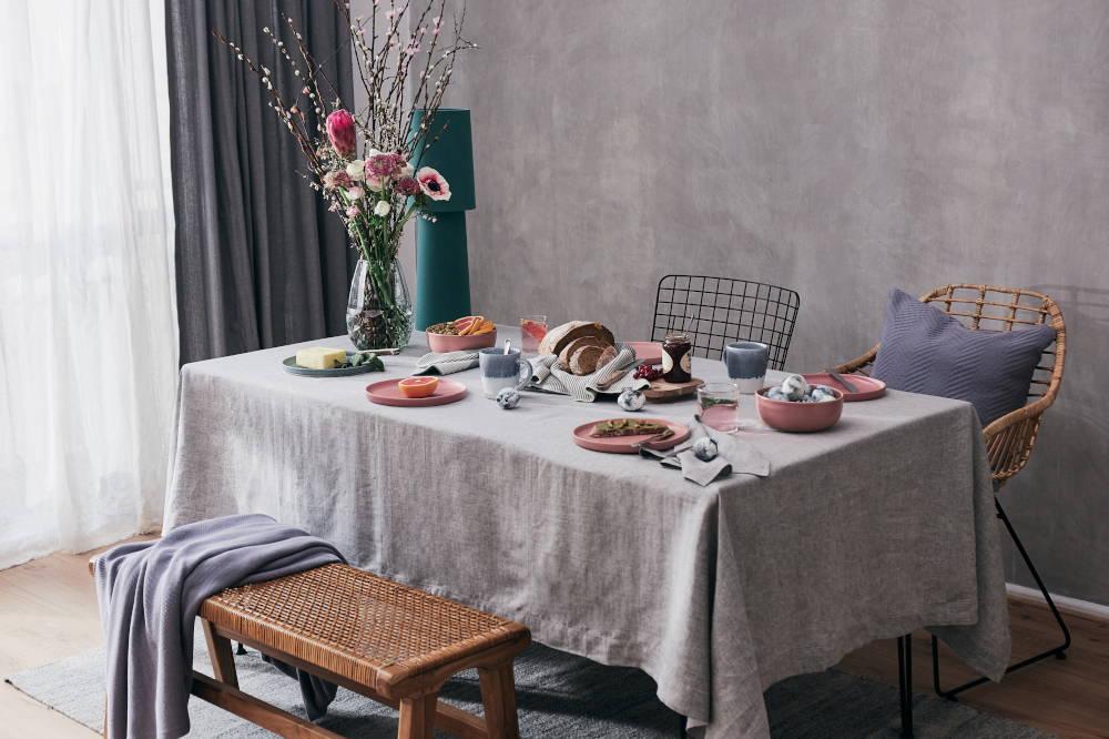 easter dining brunch table crockery pink stoneware spelt bread bouquet flowers rattan bench