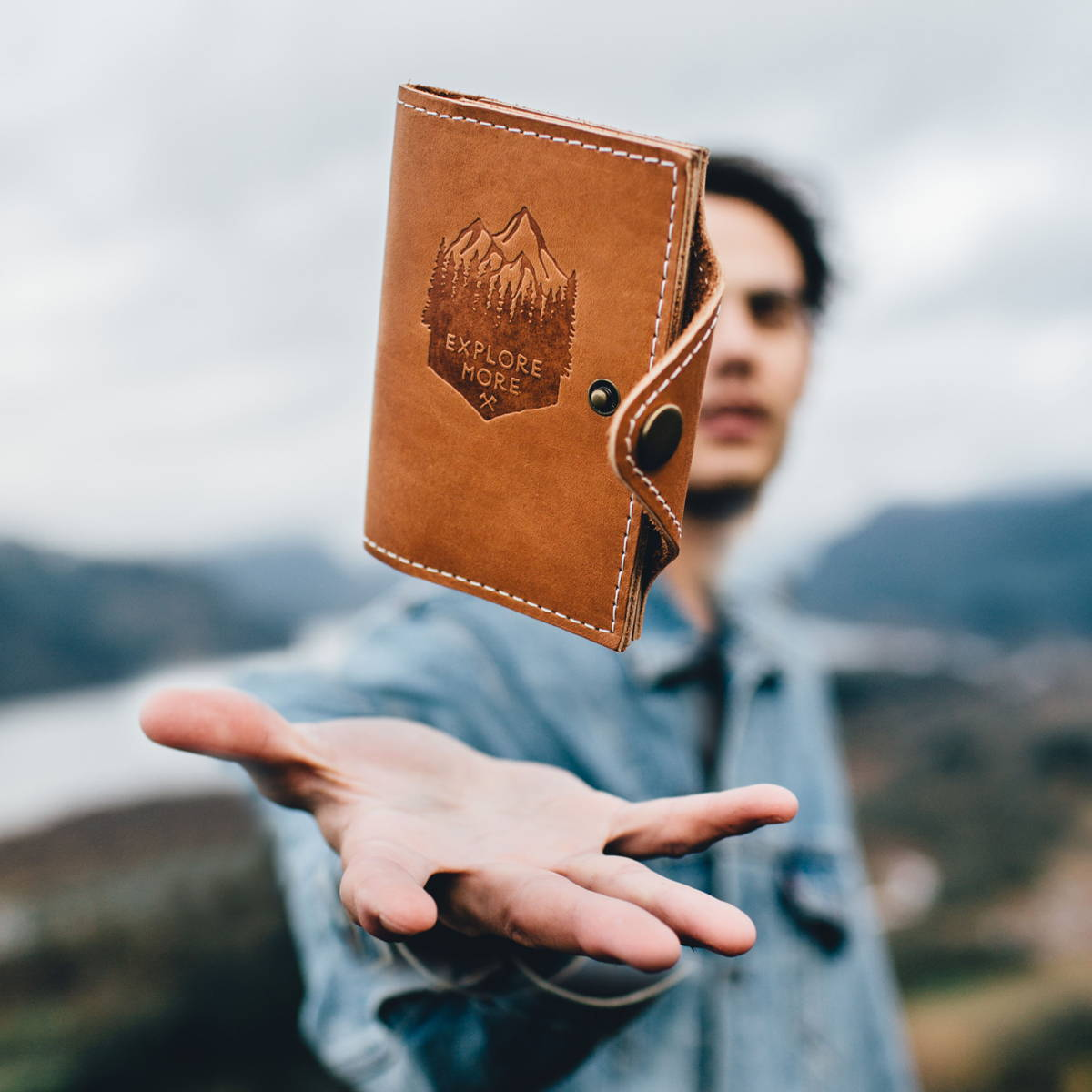 a man tossing a handmade leather journal into the air in front of a picturesque landscape scene