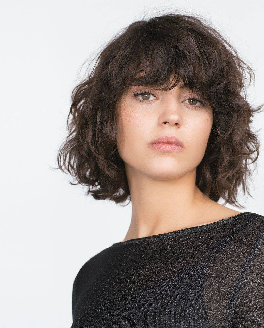 Woman with curly hair and bangs