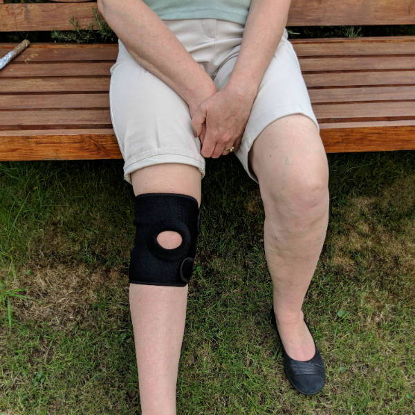 woman sat on bench wearing a knee support