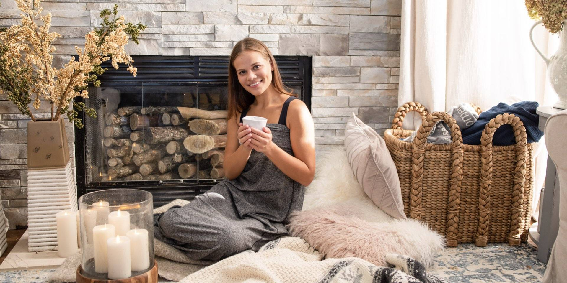 woman in sleep pod holding cup by fireplace