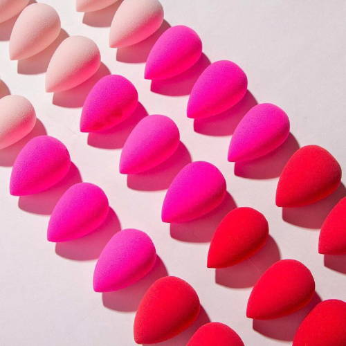 Three lines of red, pink and peach beauty blender sponges