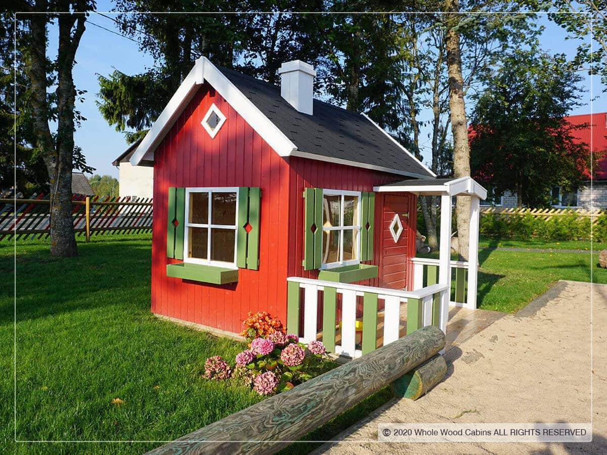 Wooden playhouse with red walls and green details and black roof in a garden by WholeWoodPlayhouses