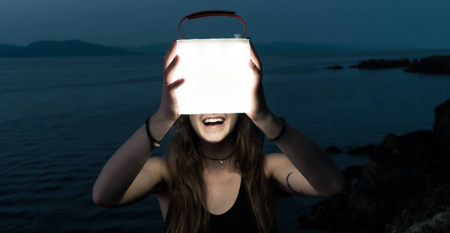 Woman holding lit up lantern infront of her face.