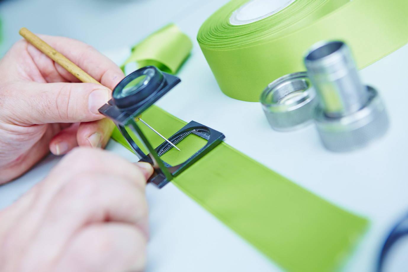 A technician sampling a strip of green fabric.