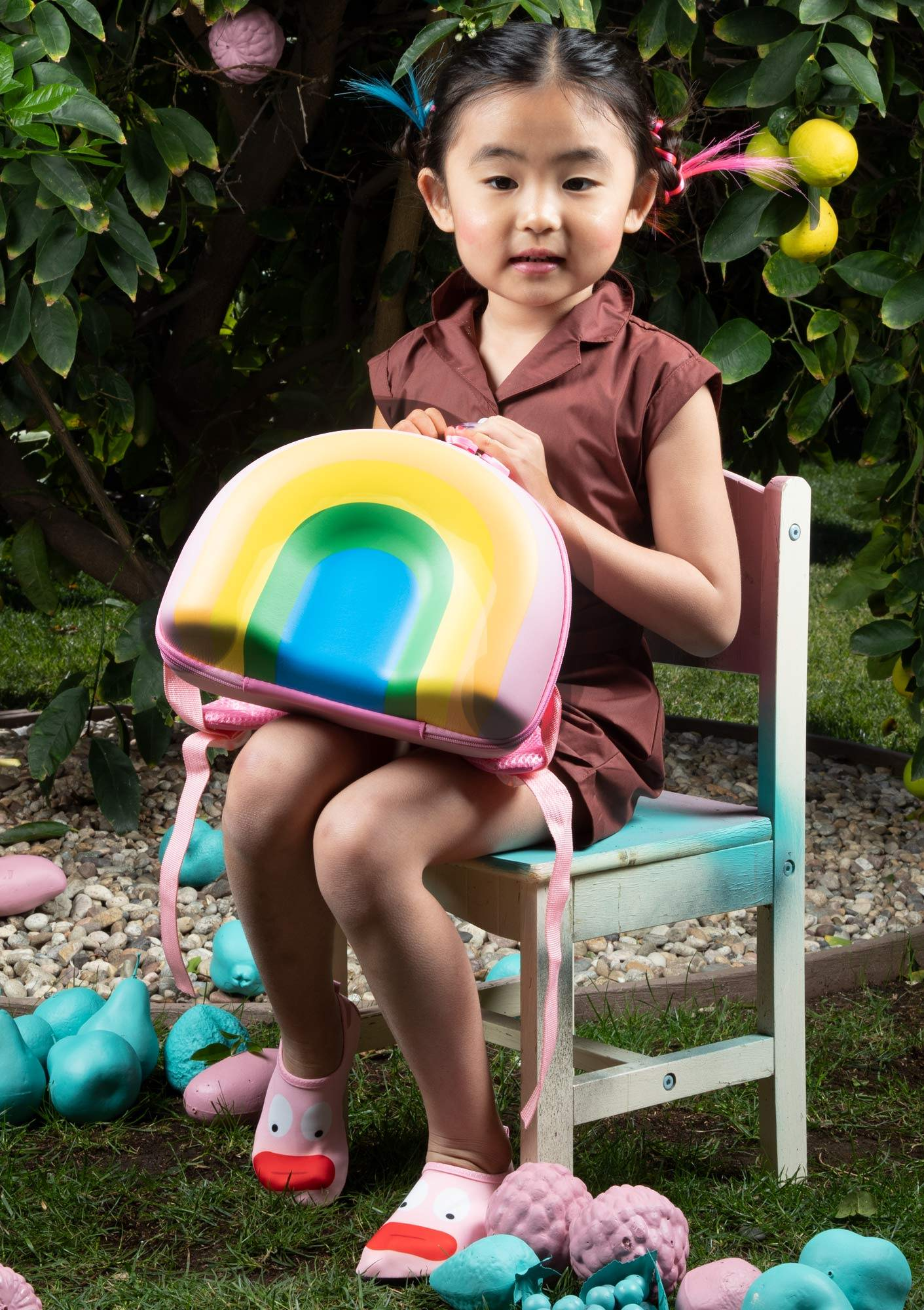 Young girl sitting on a chair with a rainbow backpack