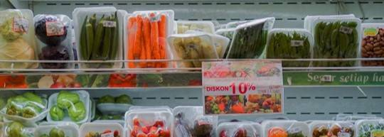 A variety of fruit and vegetables wrapped in plastic packaging