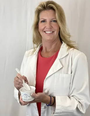 Owner, Sisan Scherer, holding a cup of Heavenly Hash Ice Cream