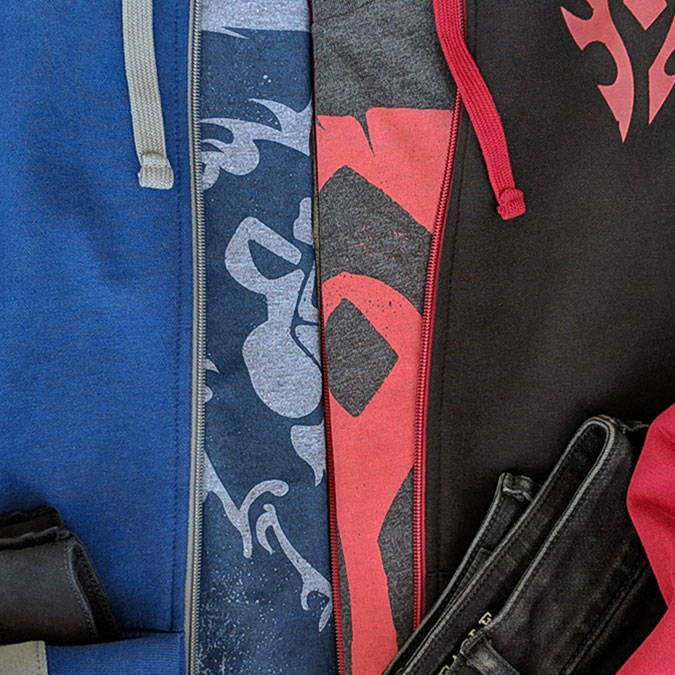 Photo showing a collection of Horde and Alliance hoodies and shirts