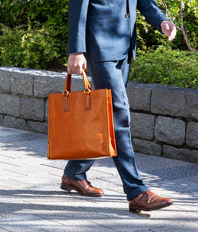 ビジネススーツ姿の土屋鞄スタッフが革のビジネスバッグを持って歩く
