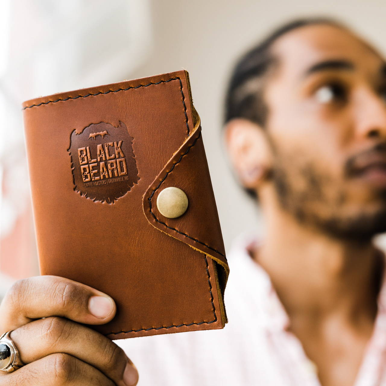 man holding leather branded passport cover
