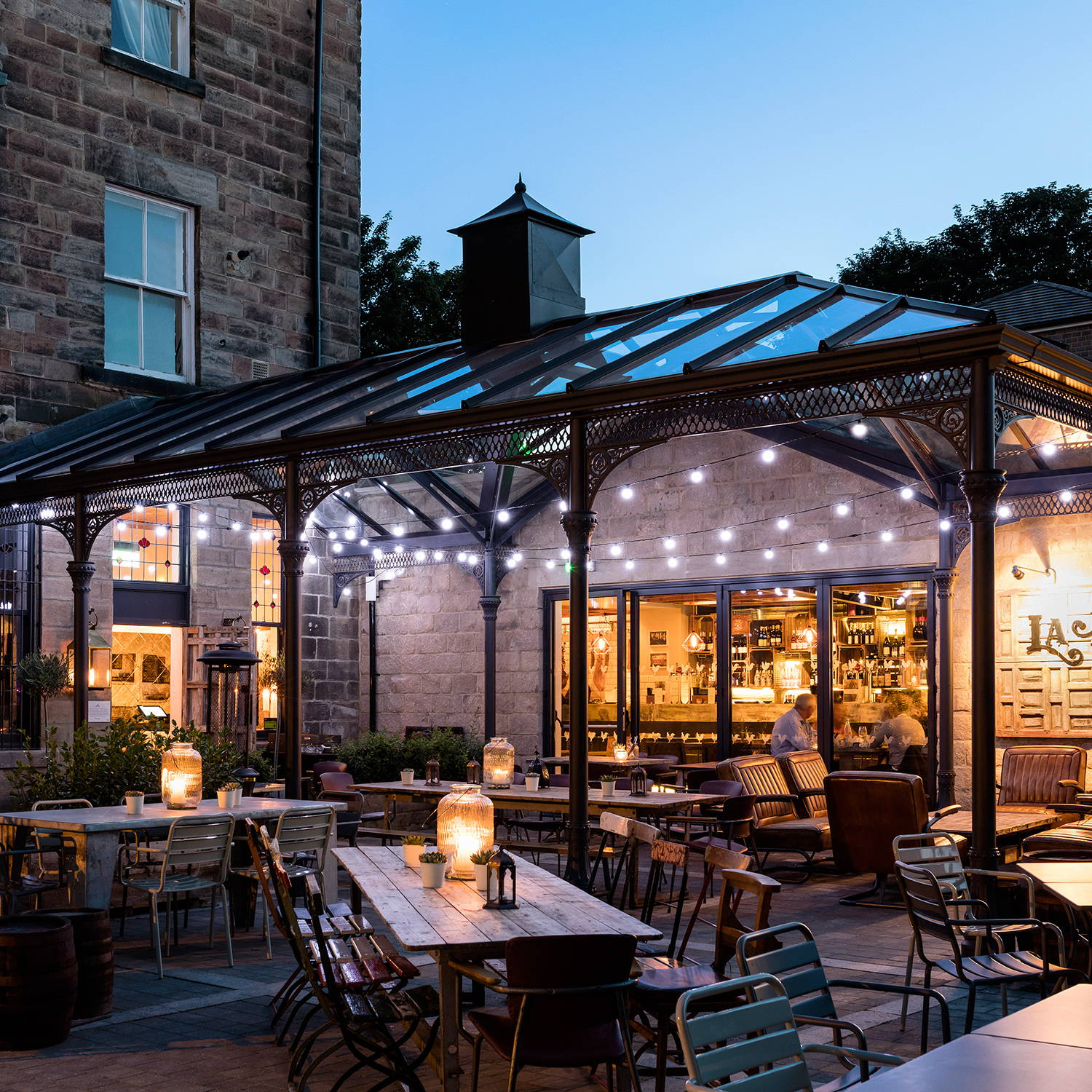 An outdoor restaurant space with tables and a conservatory dressed with festoon lights