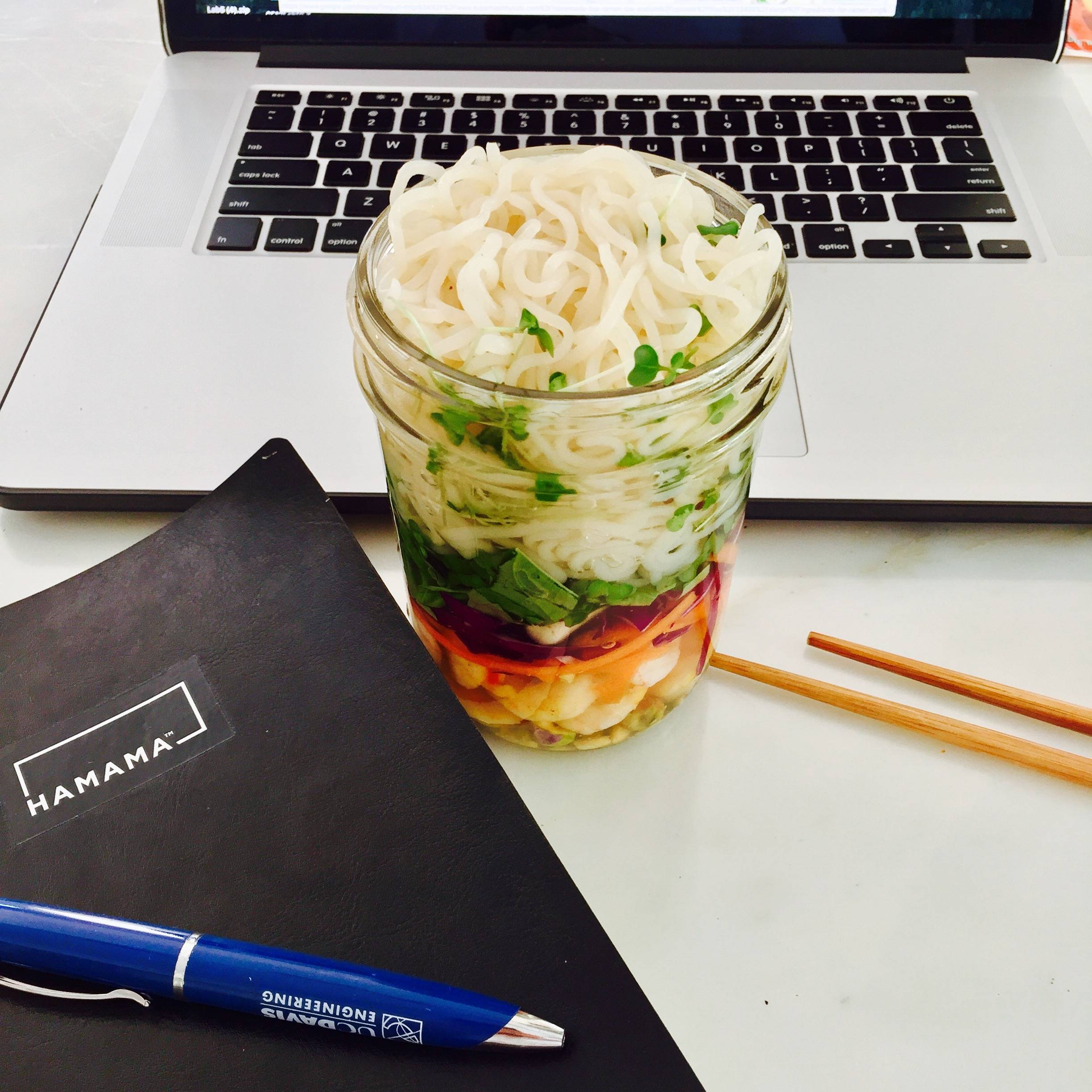 Pho in a mason jar with rice noodles, carrots, pistachios, purple cabbage, basil, and broccoli microgreens.