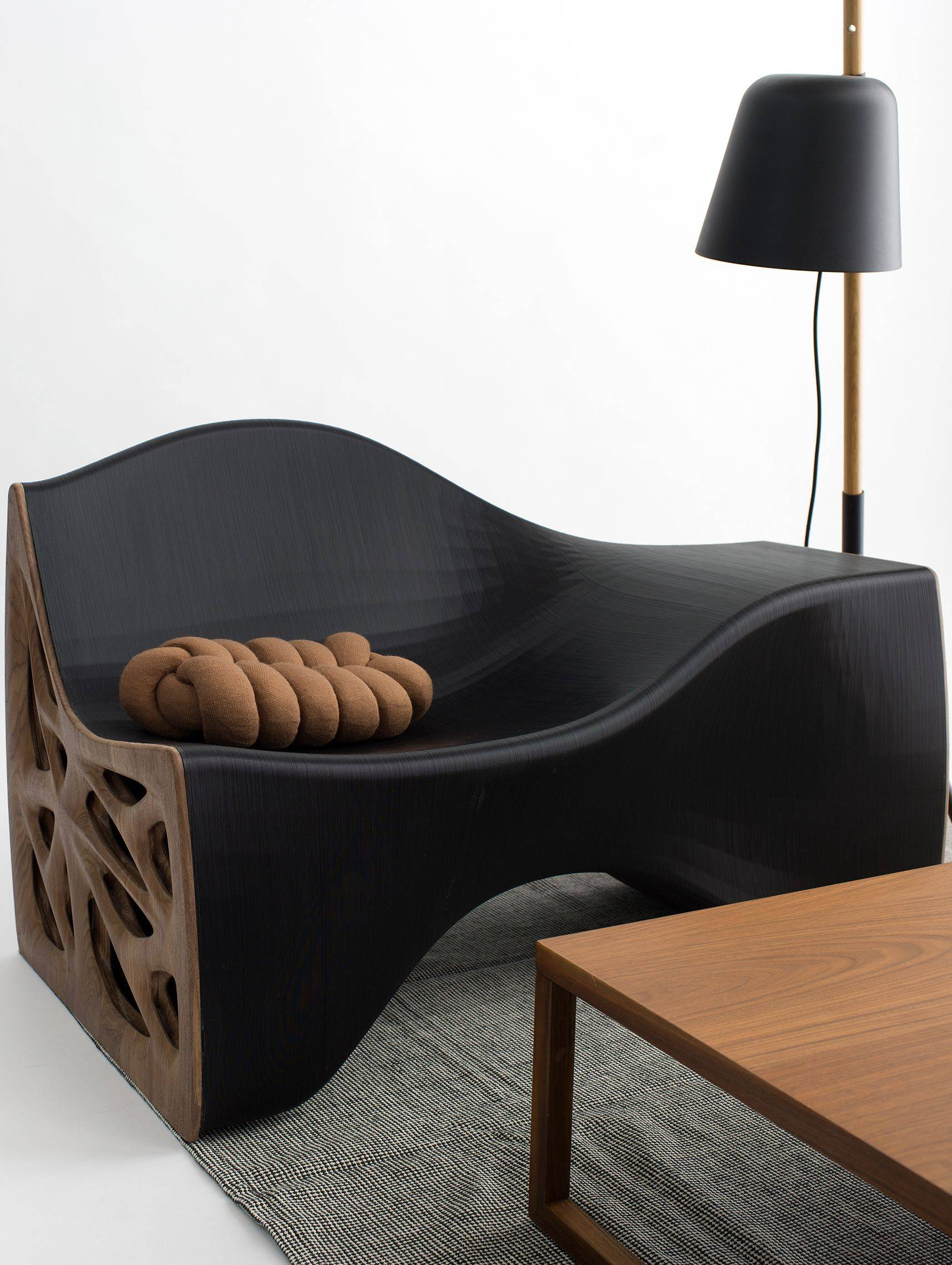 Curvy chaise lounge made of black plant resin and hardwood sides in front of coffee table
