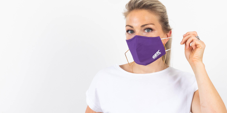 A woman wearing a purple GRTC mask.