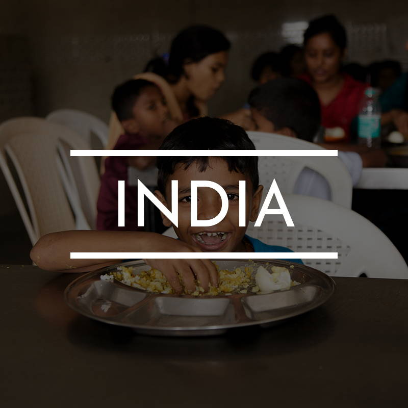 """INDIA"" is written on top of and image of a  young Indian boy sitting at a table eating rice"