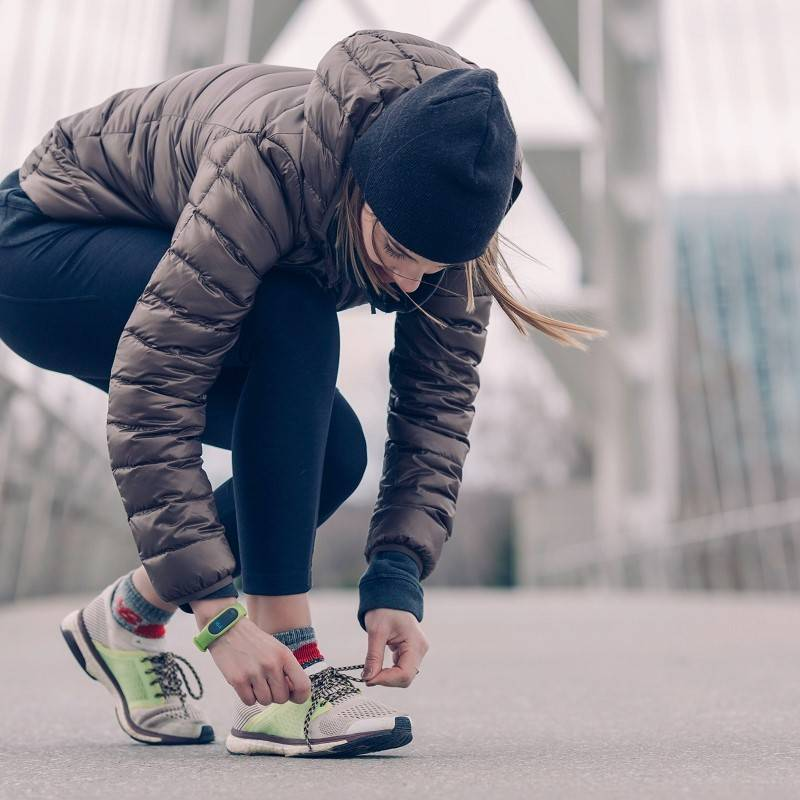 A lady in a beanie, puffer jacket and running leggings, is lacing up her trainers for a city run
