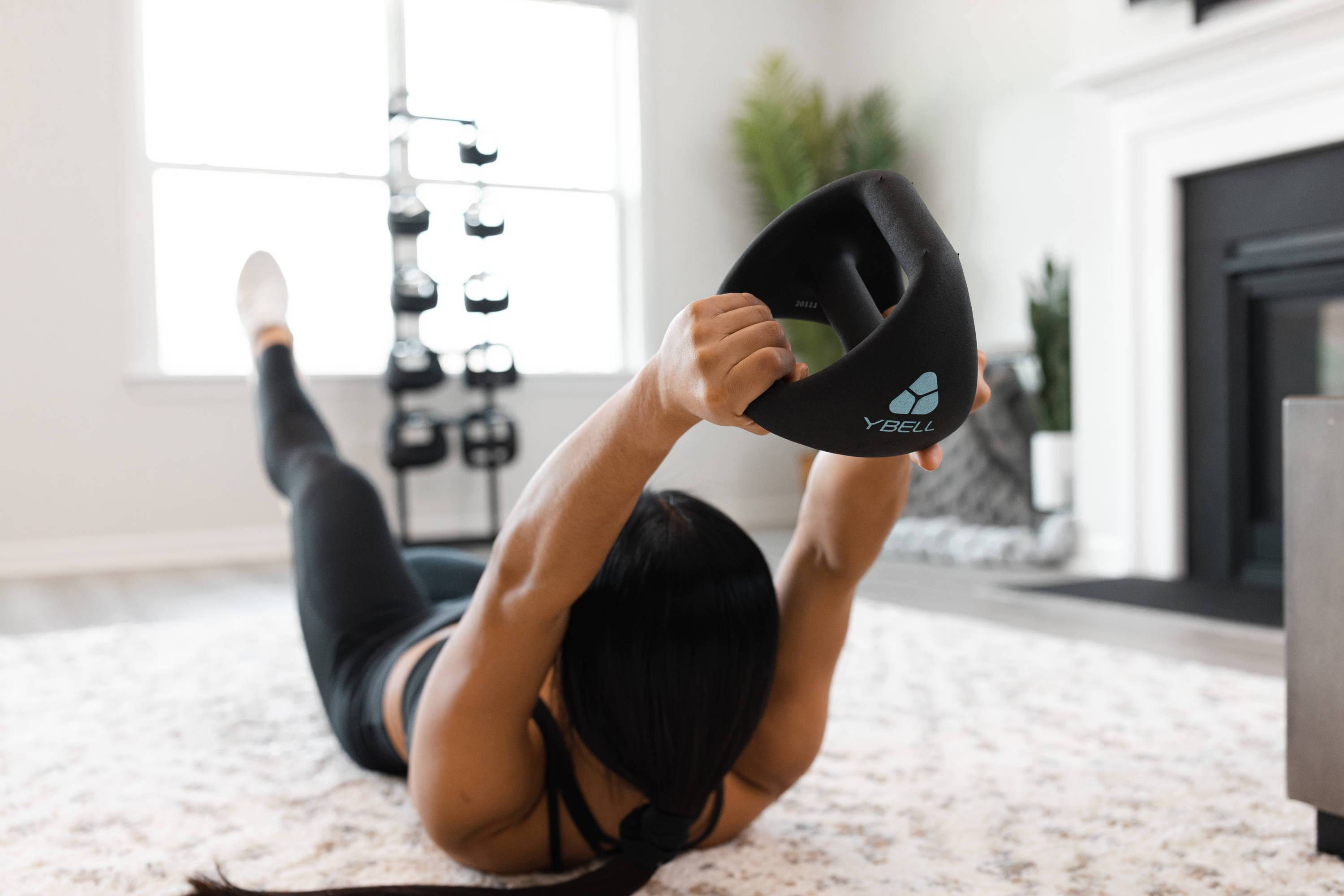 A female athlete works out with YBells in her home gym.