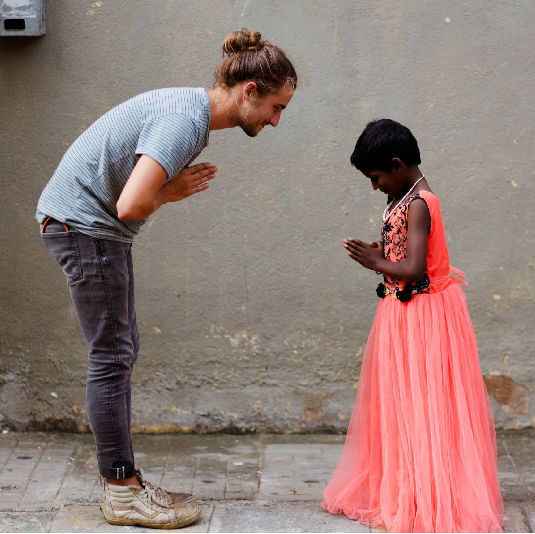 a white male in a green shirt and black pants and a young Indian girl in a pink dress bow towards each other in namaste