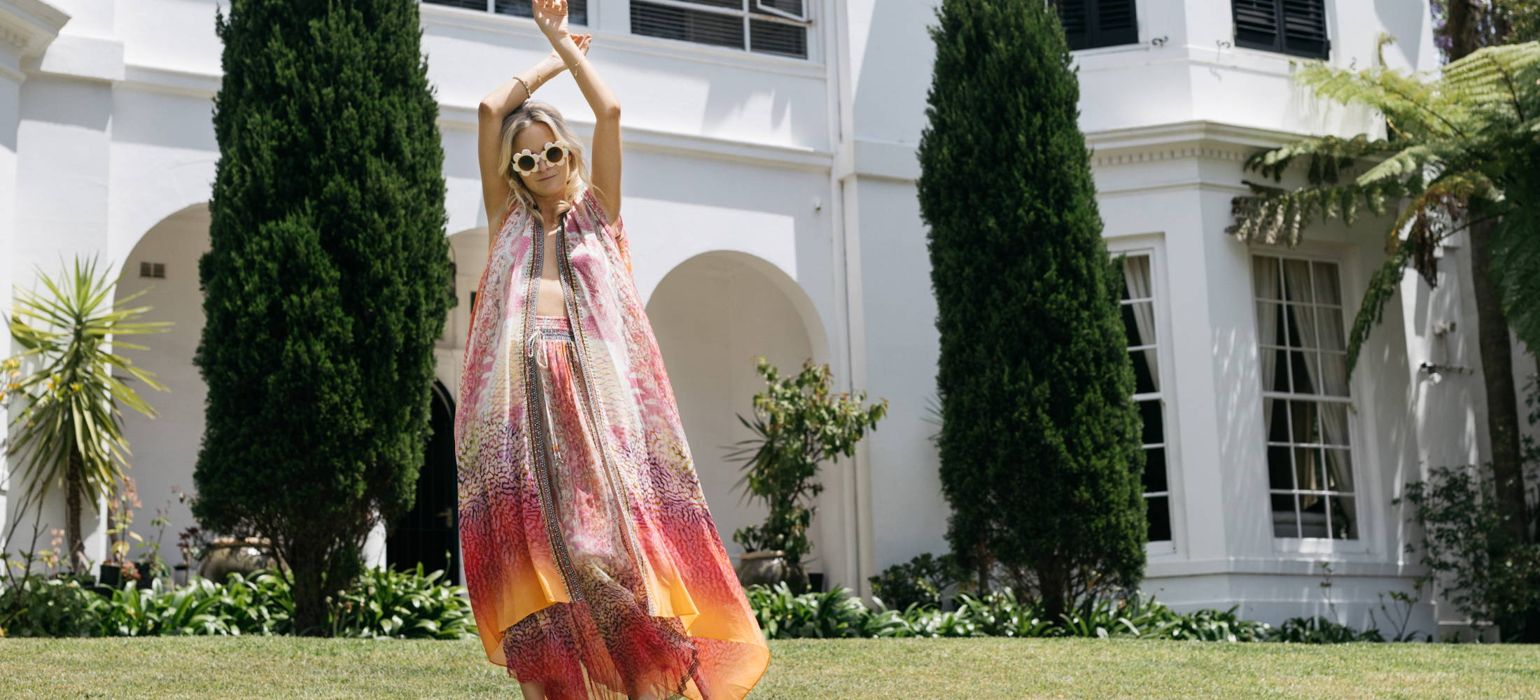 Model in CAMILLA pink and orange printed layer and pants in front of house.