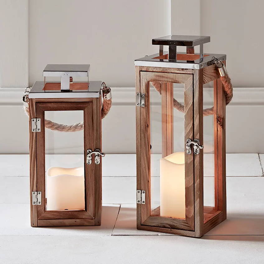 Two Salcombe wooden lanterns positioned indoors on the floor
