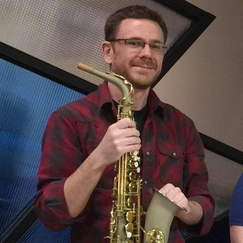 Saxophone Repair Specialist Ryan Walker of MusicMedic holding a Wilmington Alto Sax