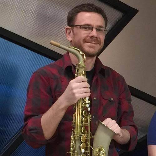 Saxophone Repair Specialist Ryan Walker of MusicMedic holding a Wilmington Alto Sax
